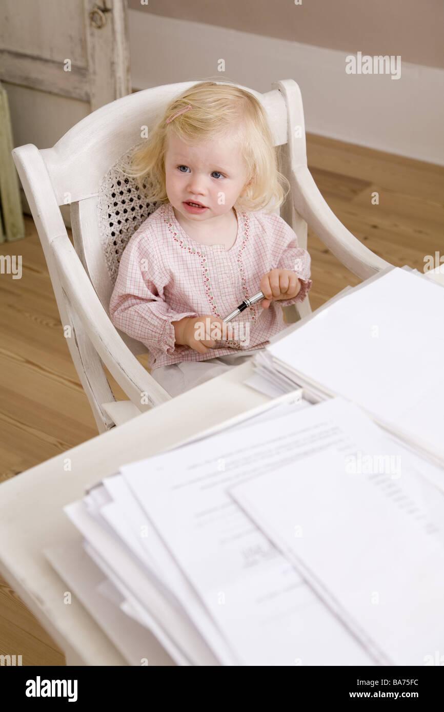 Studi desk sedia toddler sit gioca la carta della penna di fianco sintesi semi-portrait appartamento uso ufficio Foto Stock