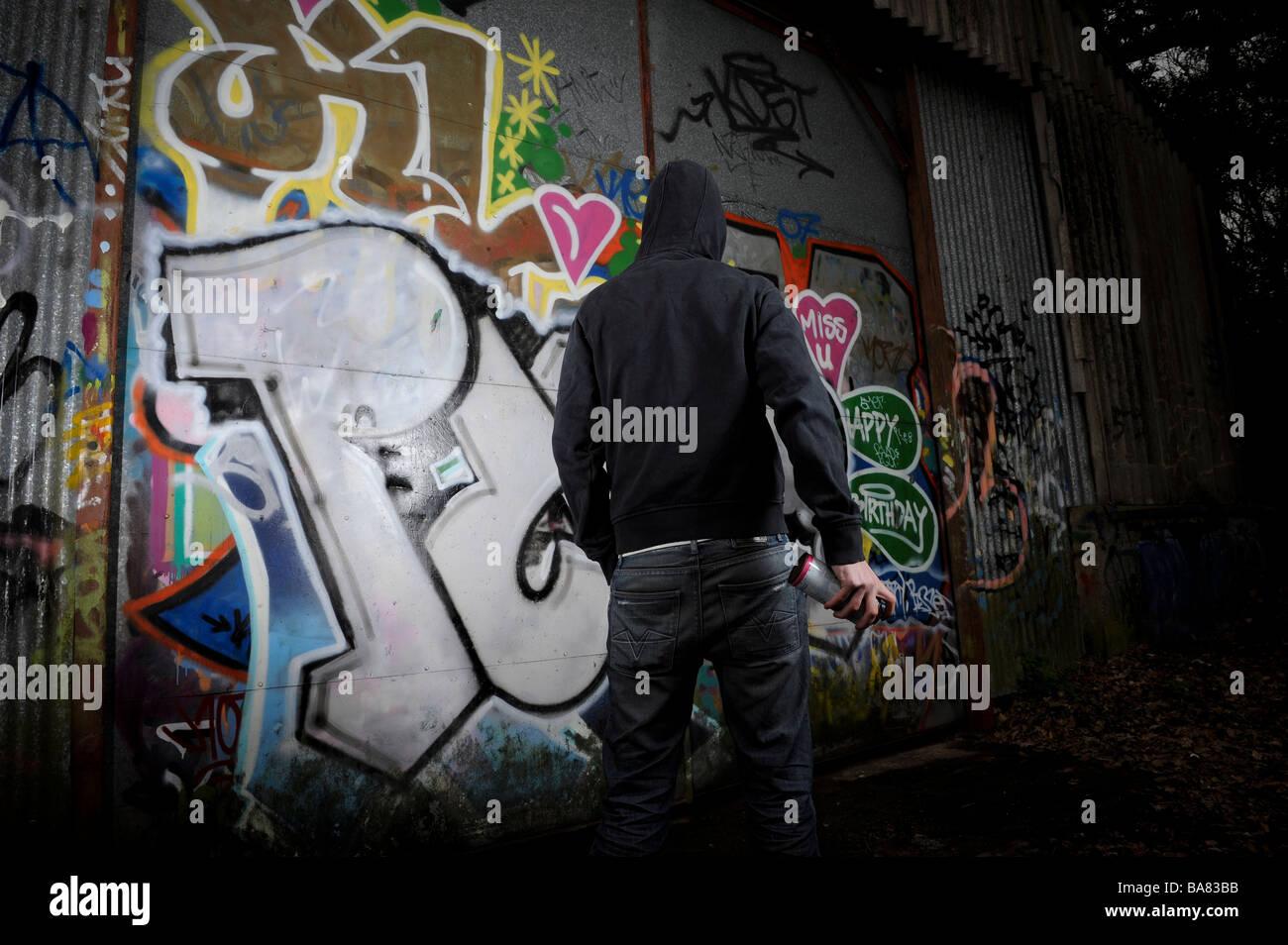 Persona in abiti scuri in piedi di fronte ad una superficie graffittied Immagini Stock