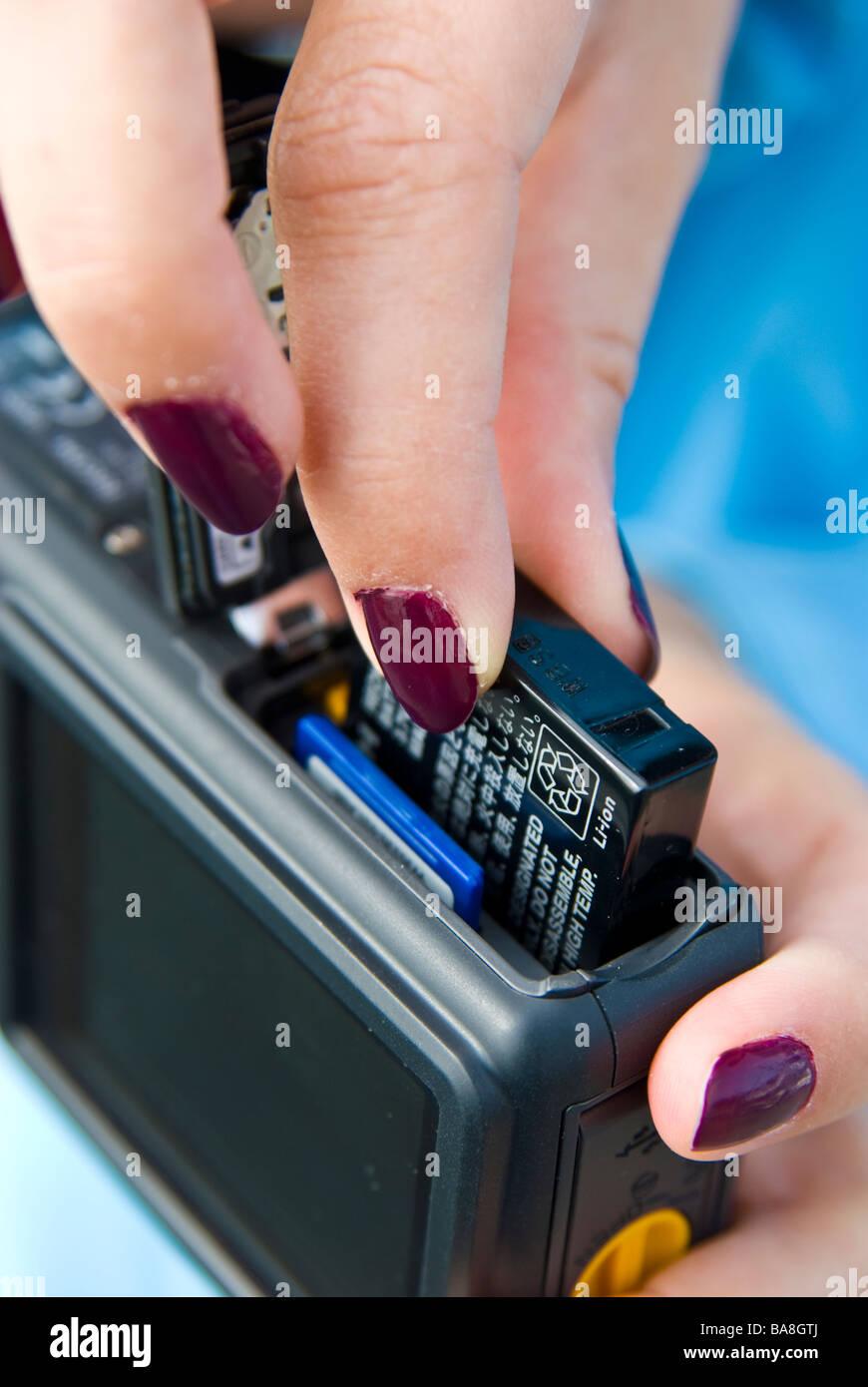 Ragazza fotocamera digitale compatta che mostra la batteria e chip di memoria della scheda di memoria | dito Batterie Immagini Stock
