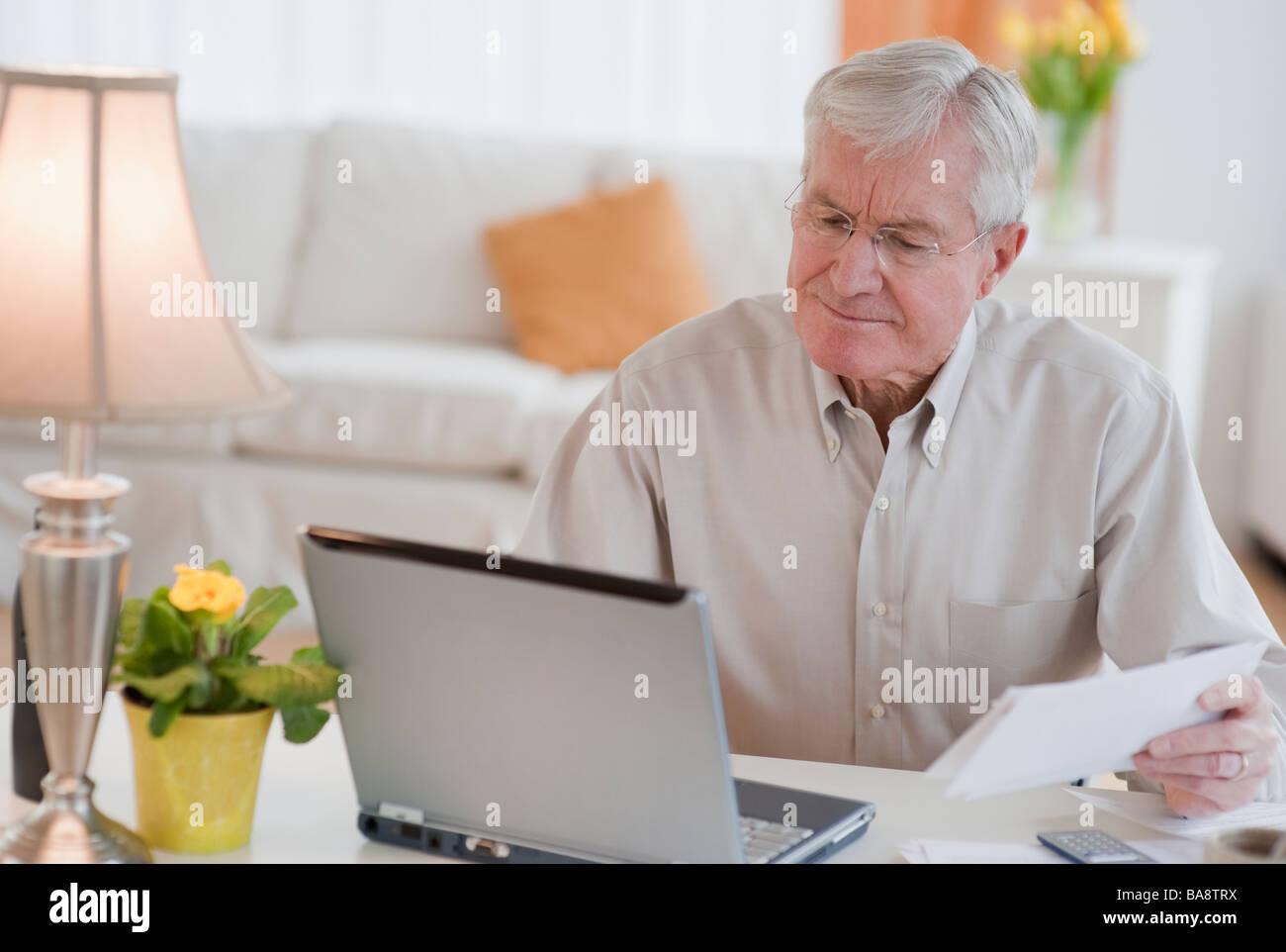 Uomo senior di pagare le bollette online Immagini Stock