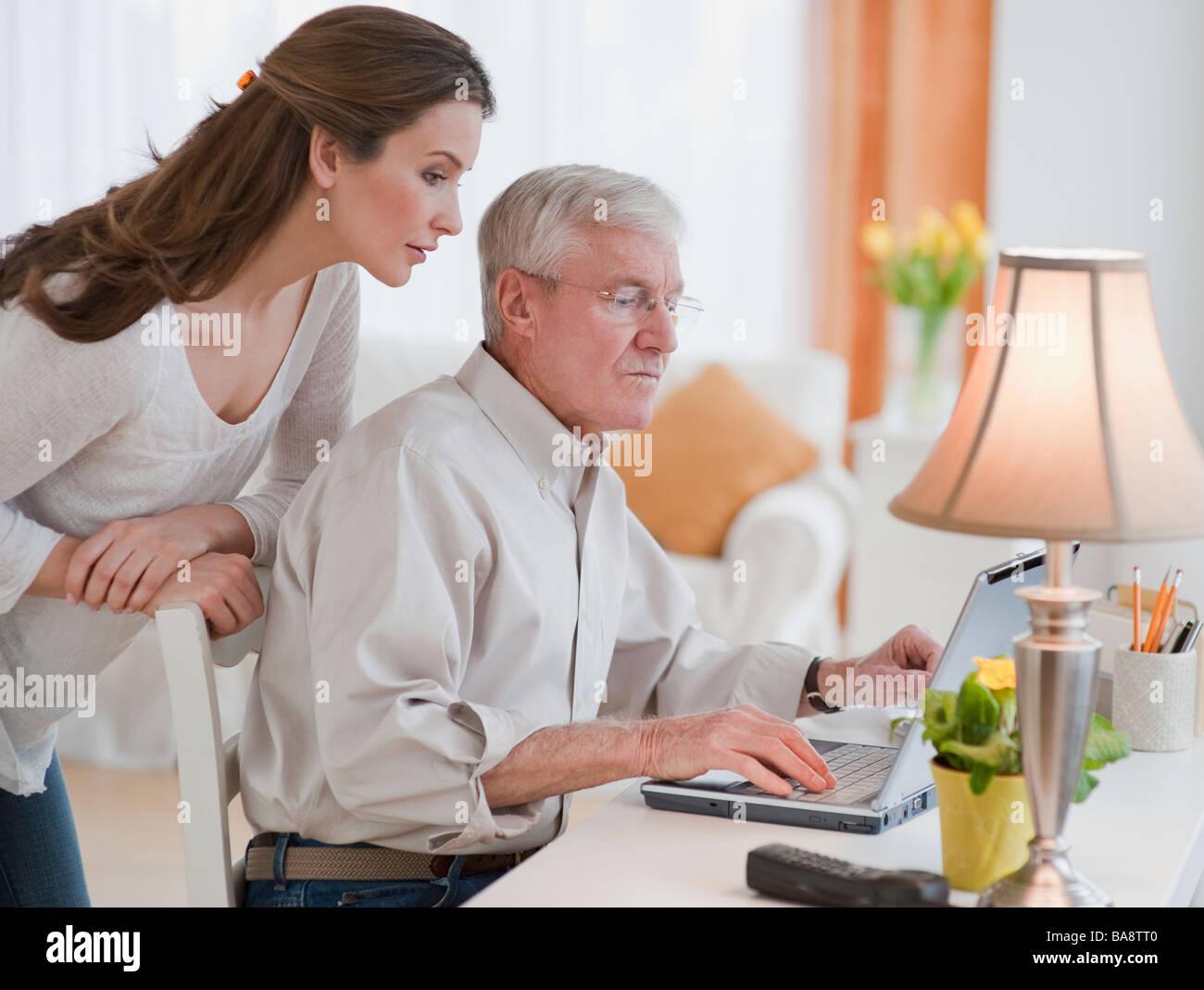 Figlia aiutando padre senior con il computer Immagini Stock