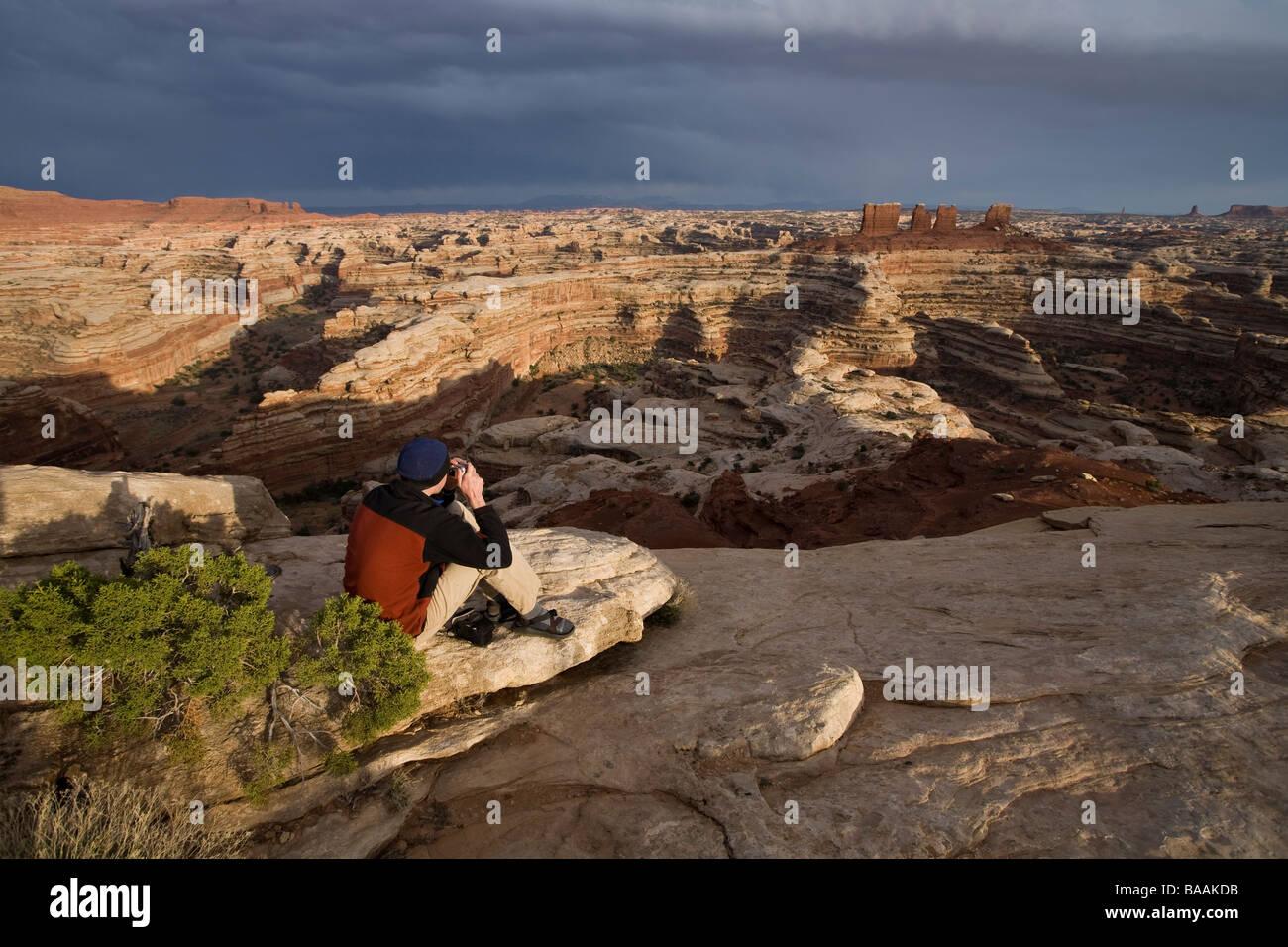 Uomo che guarda con il binocolo nel labirinto sezione dal bordo della scogliera nel Parco Nazionale di Canyonlands, Immagini Stock