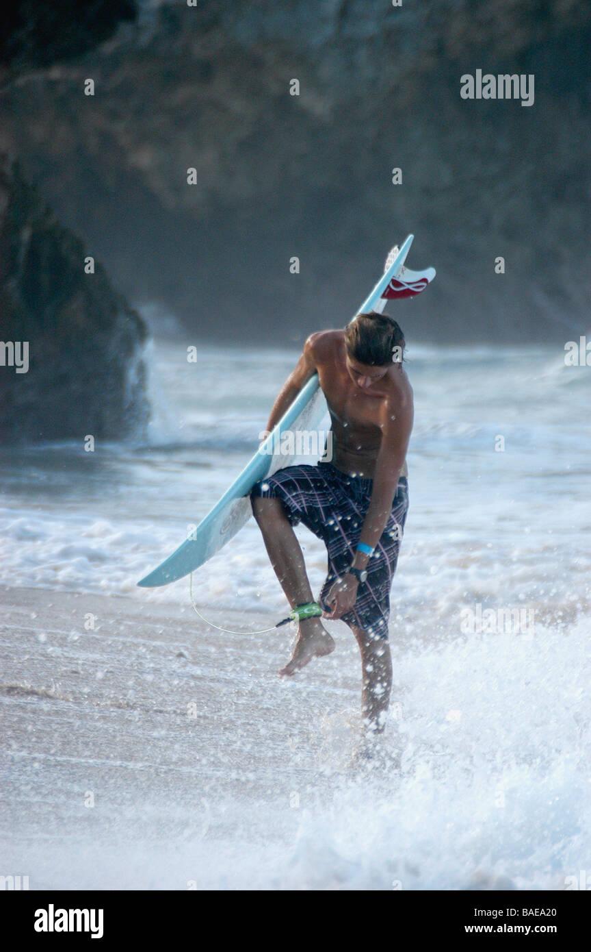 Un surfista si allenta la sua fascetta di surf dopo provenienti dal mare Foto Stock