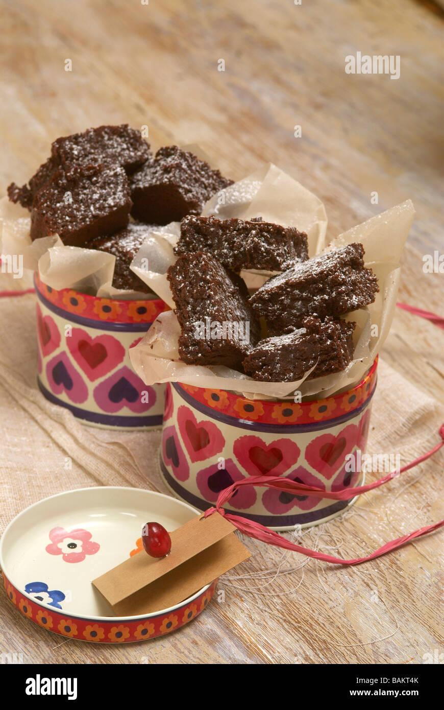 Brownie al cioccolato in lattine circondato da carta oleata Immagini Stock