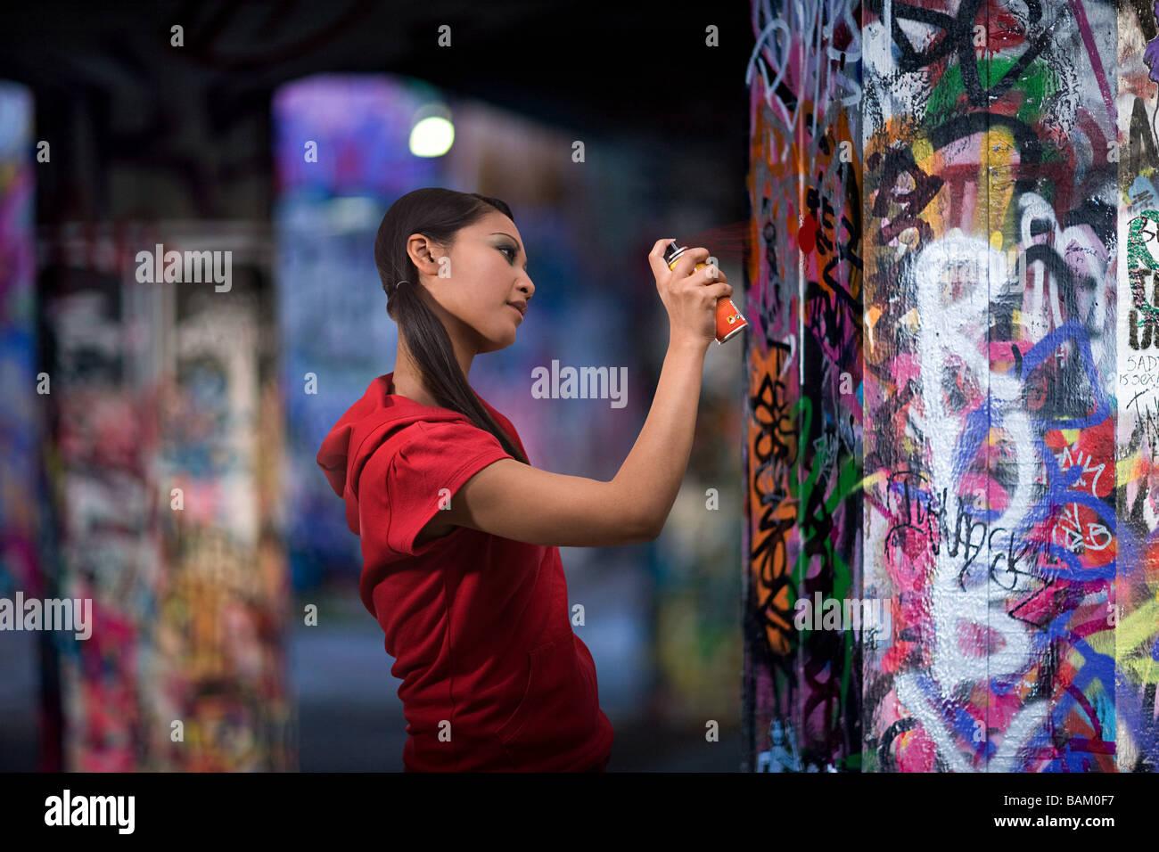Una giovane donna graffiti di spruzzatura Immagini Stock