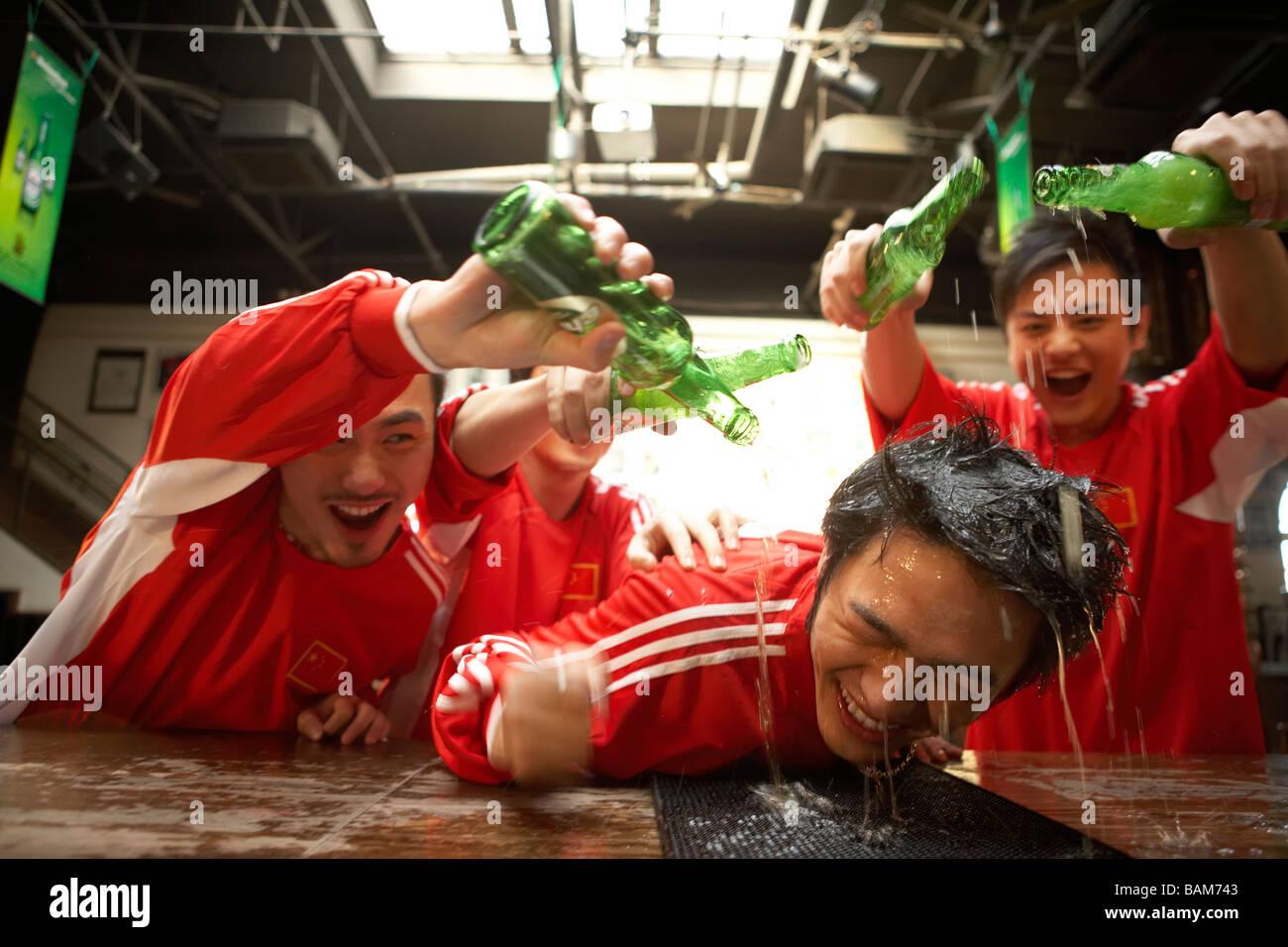 Giovani uomini versando alcool su Giovane Uomo appoggiato sulla barra Immagini Stock