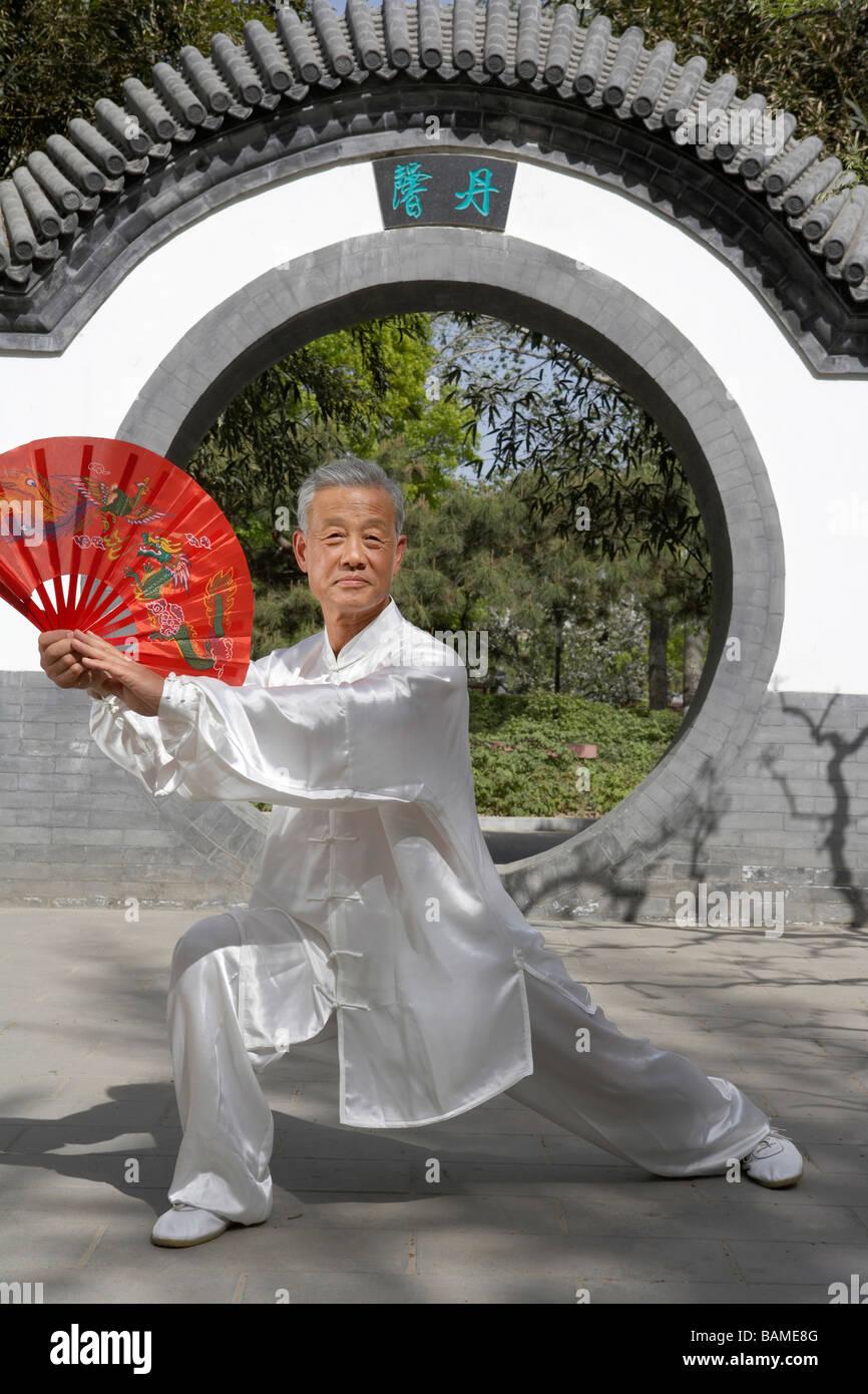 Uomo anziano praticante di arti marziali con un ventilatore Immagini Stock