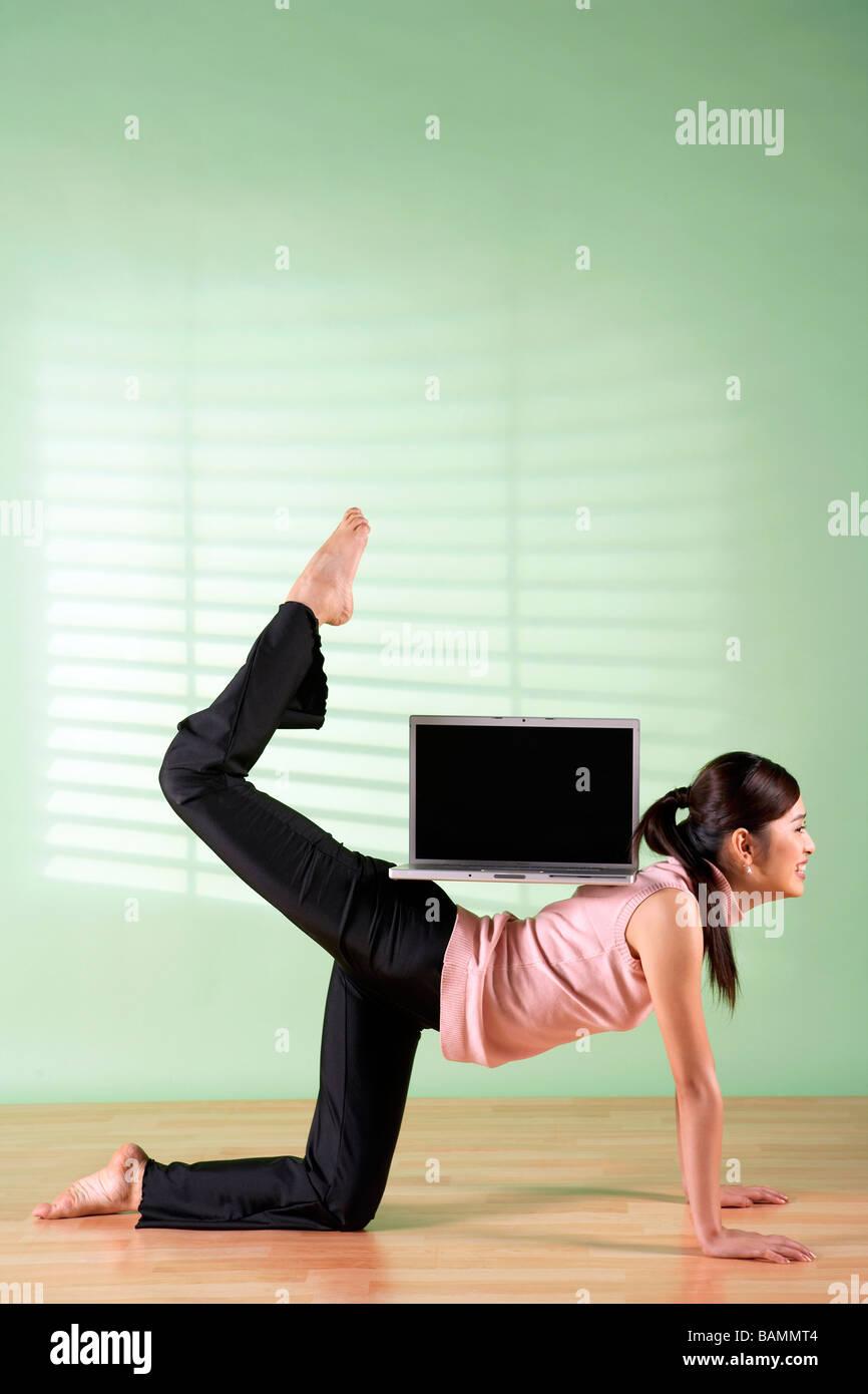 Bilanciamento donna Computer portatile sulla sua schiena Immagini Stock
