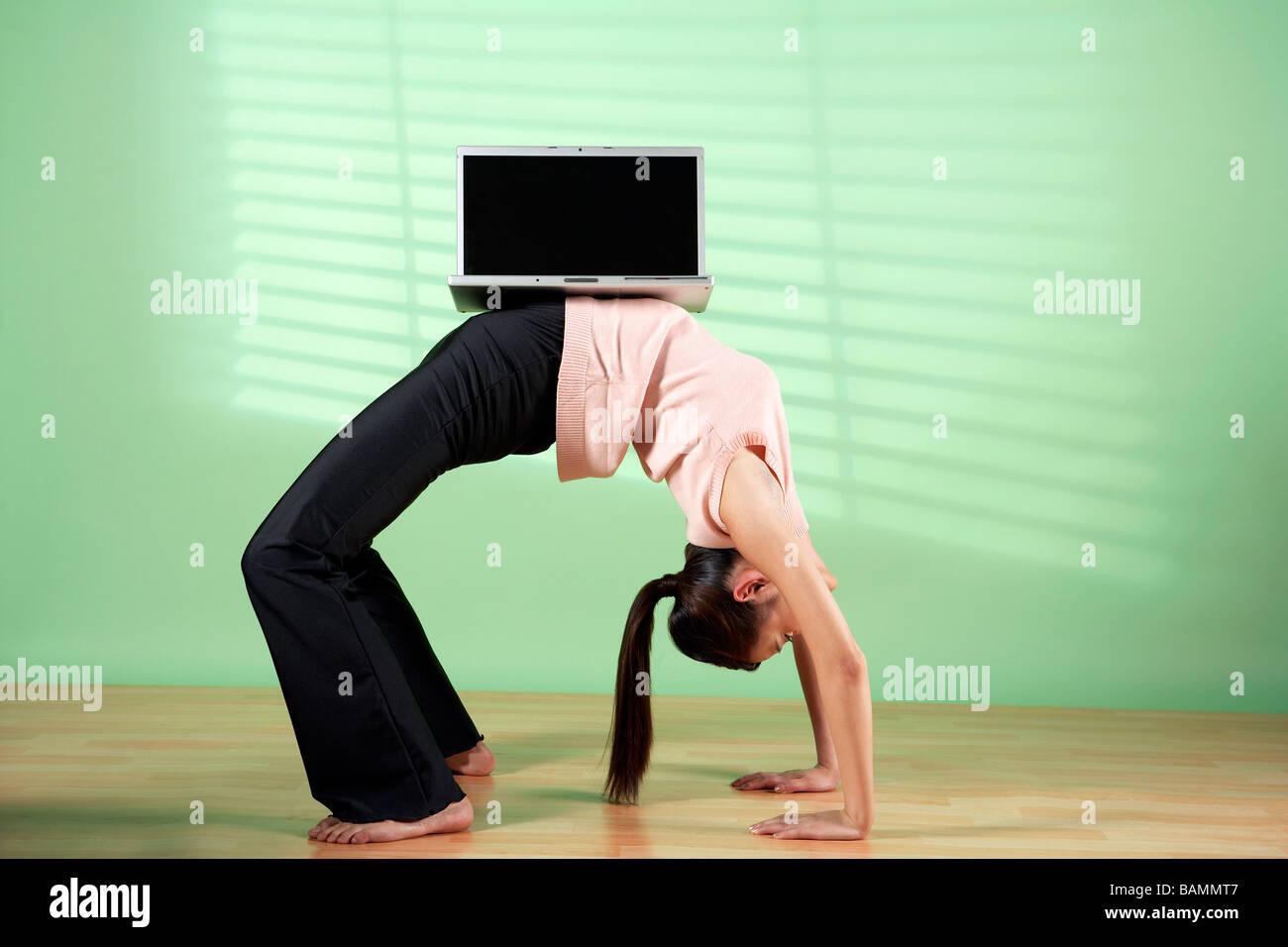 Donna di bilanciamento del computer portatile sul suo stomaco Immagini Stock