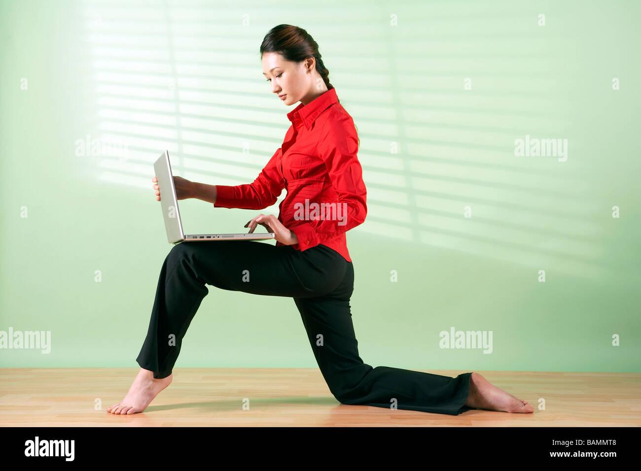 Donna con notebook computer sul suo ginocchio Immagini Stock