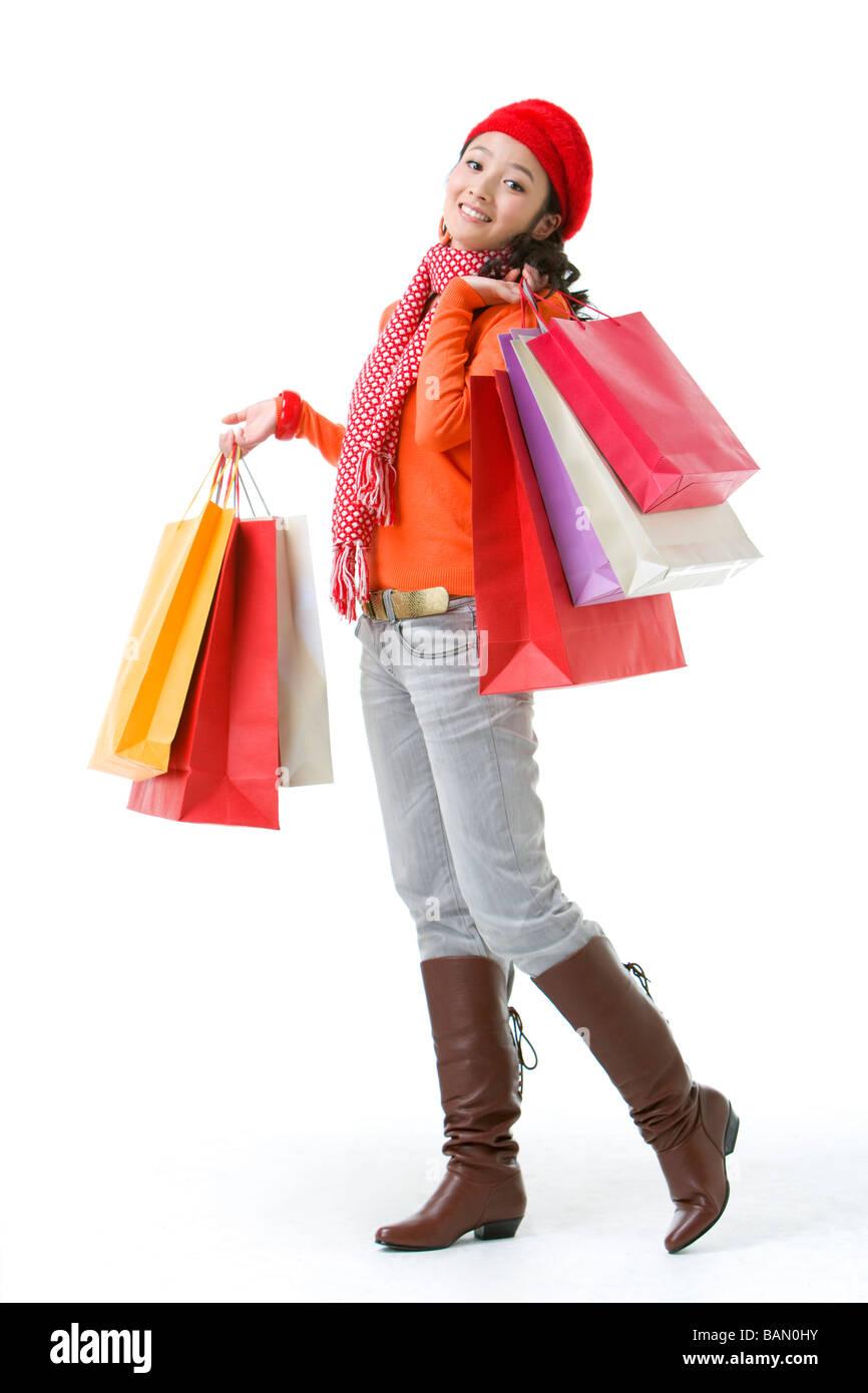 Giovane donna tenendo su borse per lo shopping Immagini Stock