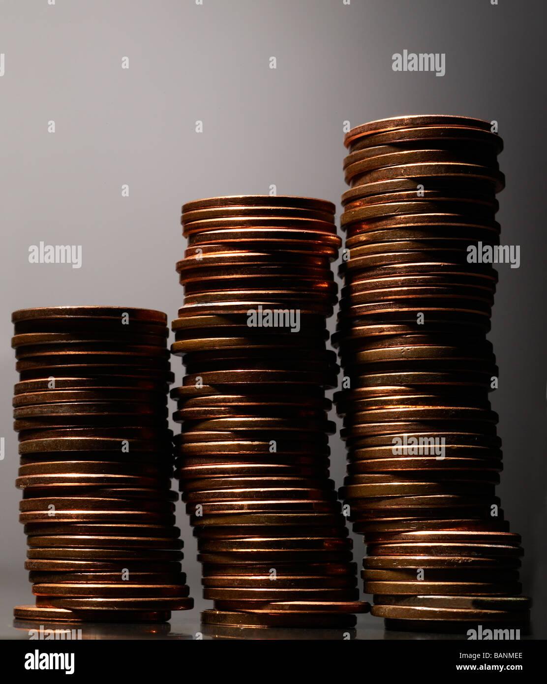 Tre pile di pochi centesimi su sfondo grigio con evidenziazione sulla sinistra Foto Stock
