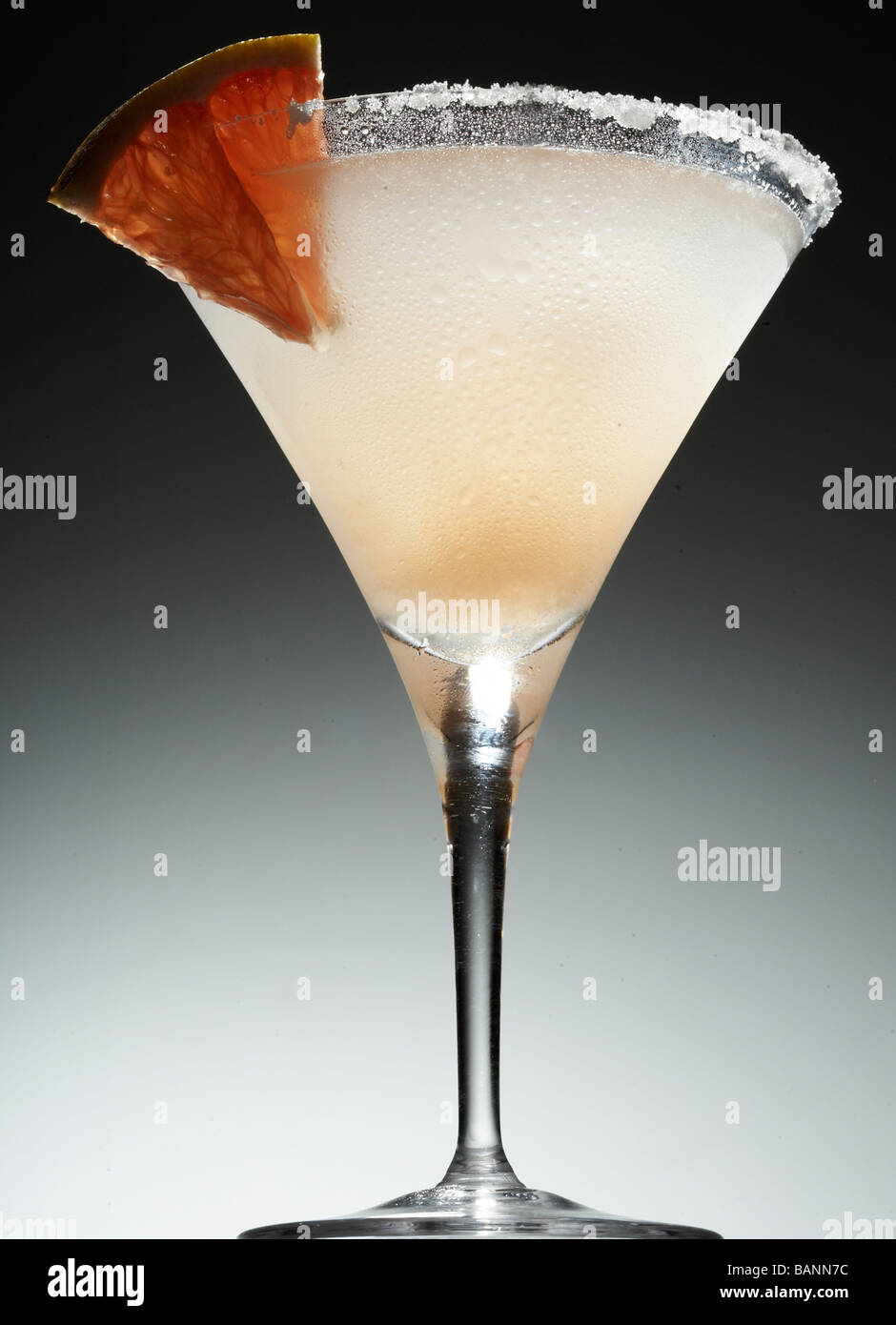 Cane salato cocktail con sale sul cerchione e il cuneo di frutta Immagini Stock
