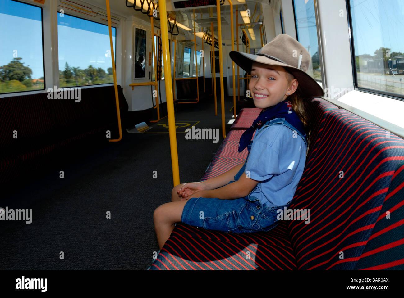 Bambino anni 10 indossando Episteme hat e indossando bandiera australiana bandana cavalcare il treno. Perth, Western Immagini Stock