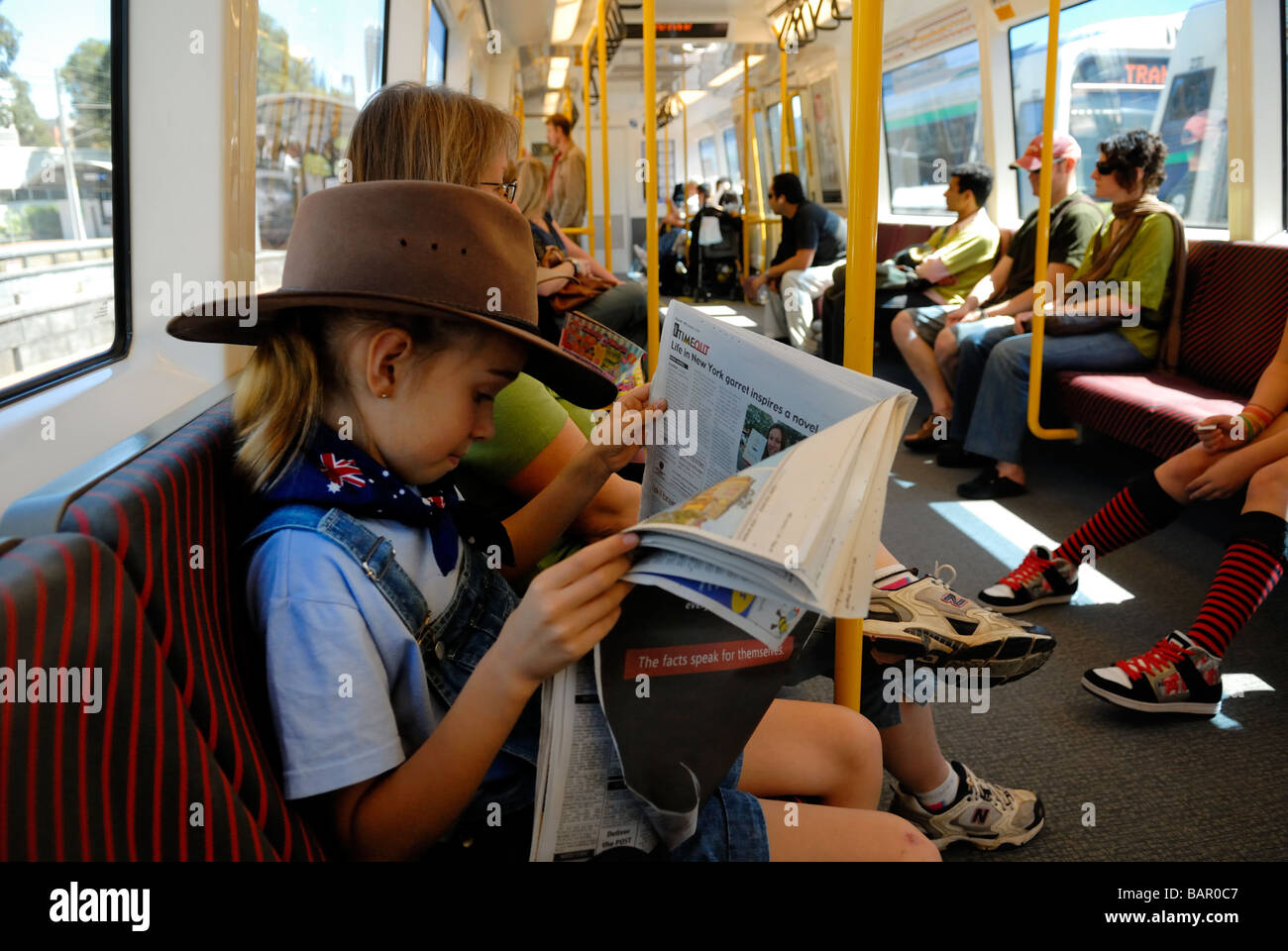 Bambino anni 10 indossando Episteme hat e bandiera australiana bandana lettura carta sul treno. Perth, Western Australia Immagini Stock