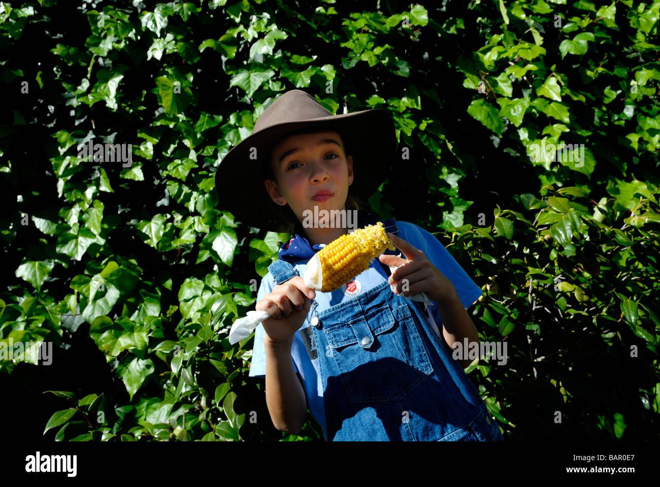 Bambino, dieci anni, indossando Episteme hat e mangiare sulla pannocchia di mais. Perth Royal Show, Perth, Western Immagini Stock
