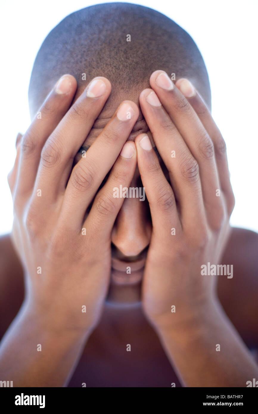 Premuto man tenendo la sua faccia nelle sue mani. Egli è di venti anni. Immagini Stock