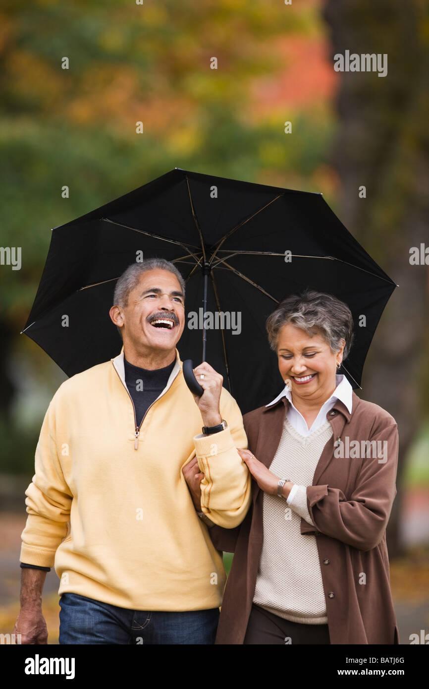 Coppia africano a piedi con ombrello in autunno Foto Stock