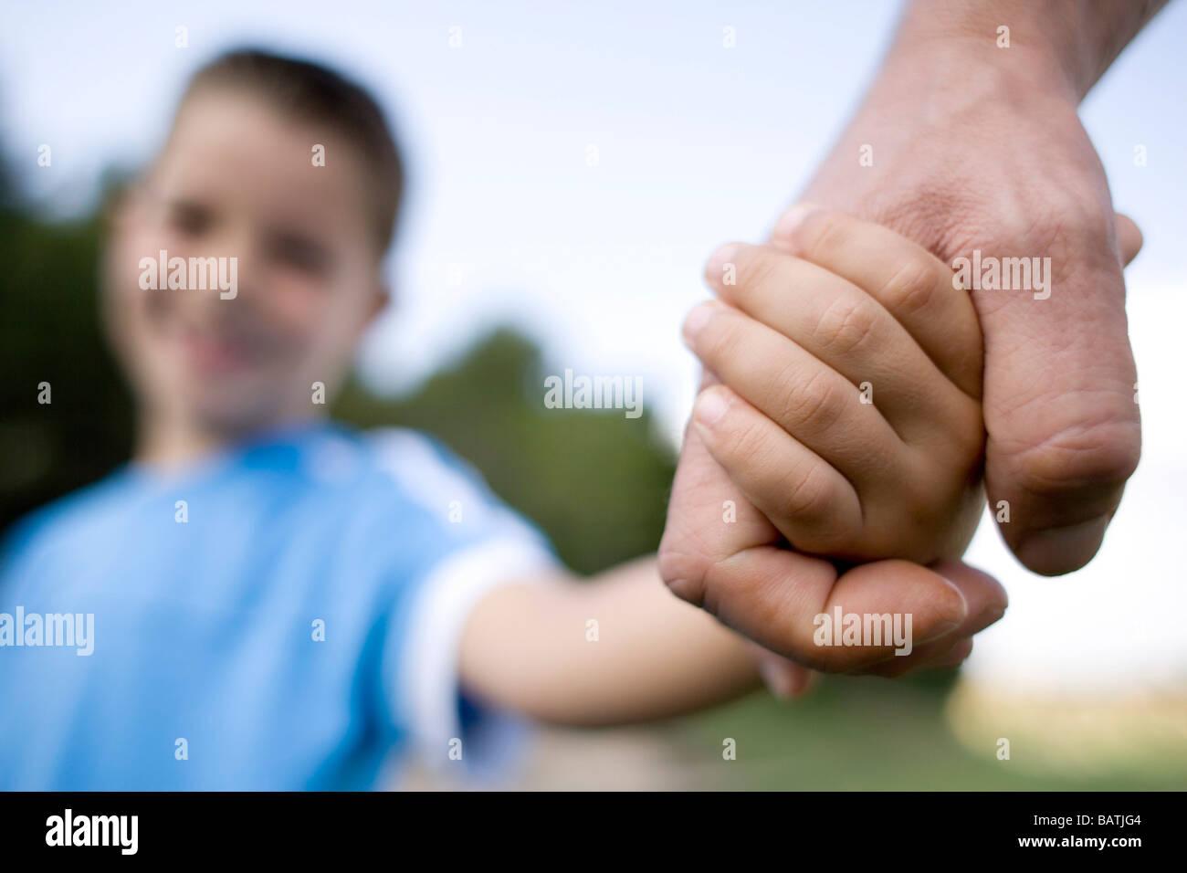 Padre e figlio tenendo le mani. Immagini Stock