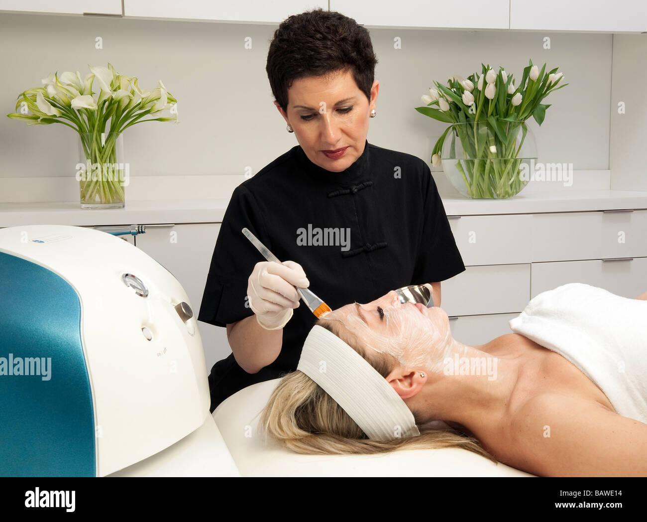 Donna di ottenere un trattamento per il viso a una spa. Immagini Stock
