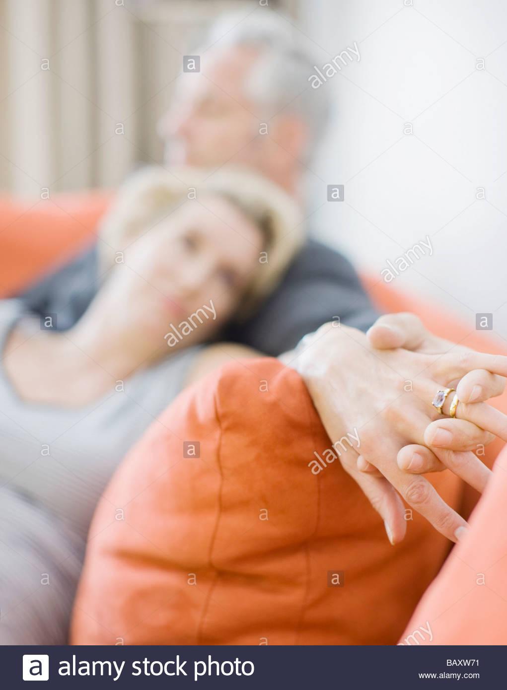 Coppia matura la posa sul divano tenendo le mani Immagini Stock