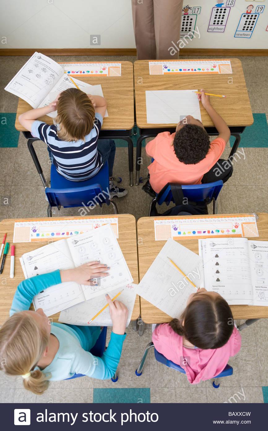 Gli studenti della scuola facendo lavorare in aula Immagini Stock