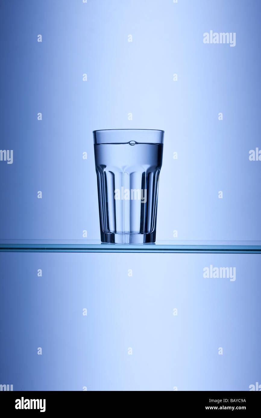 Bicchiere di acqua potabile su sfondo blu Immagini Stock