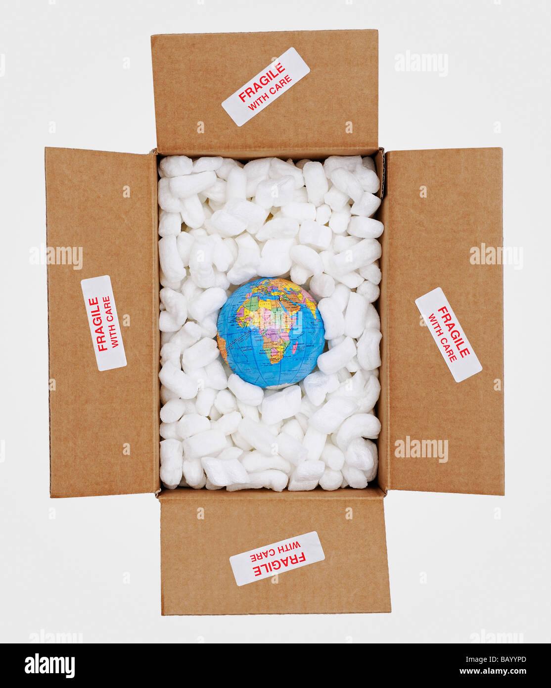 Globe di aprire una scatola di cartone circondato da imballaggio protettivo e contrassegnato come fragile Immagini Stock
