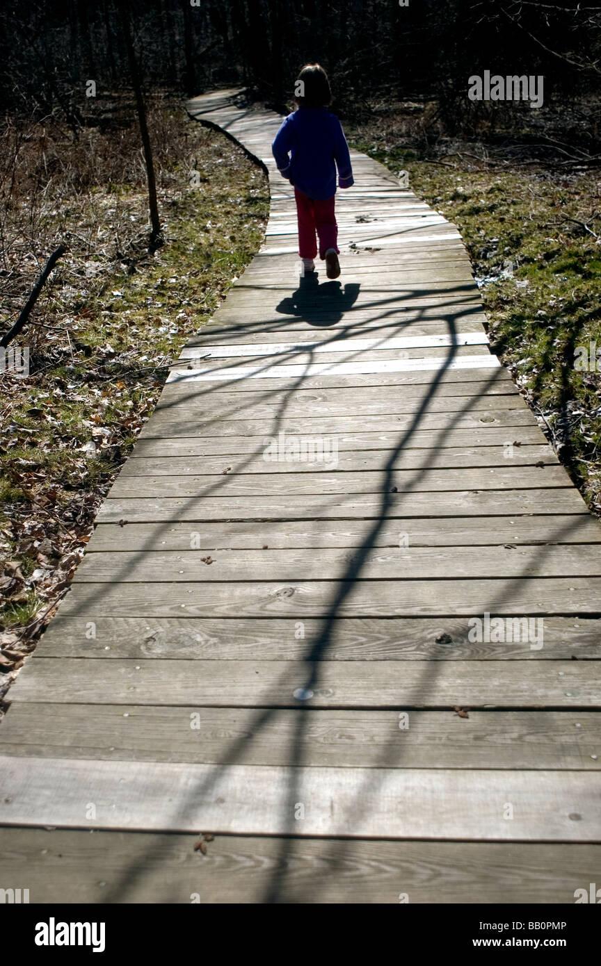 Un giovane bambino esplora la vita all'aperto come lei cammina lungo un bordo a piedi. Immagini Stock