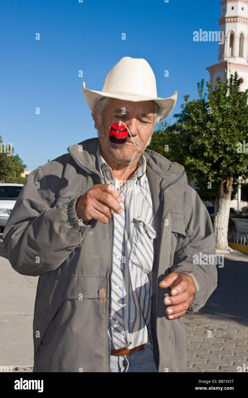 Uomo locale in El Fuerte, Messico, gioca con bambino giocattolo chiamato balero. Vi è una sfera su una stringa Immagini Stock