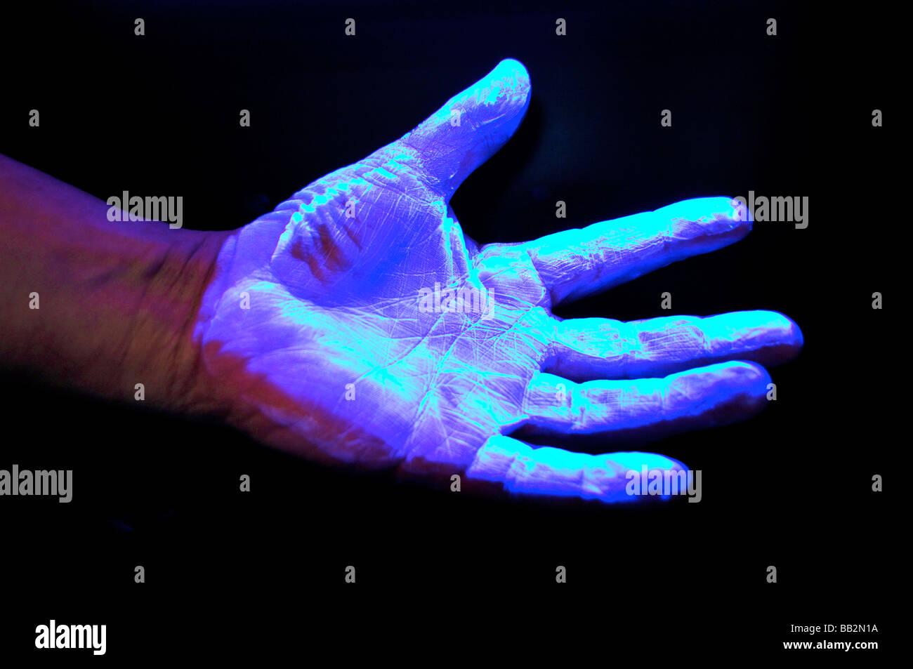 Mano sotto la luce ultra violetta su sfondo nero Immagini Stock