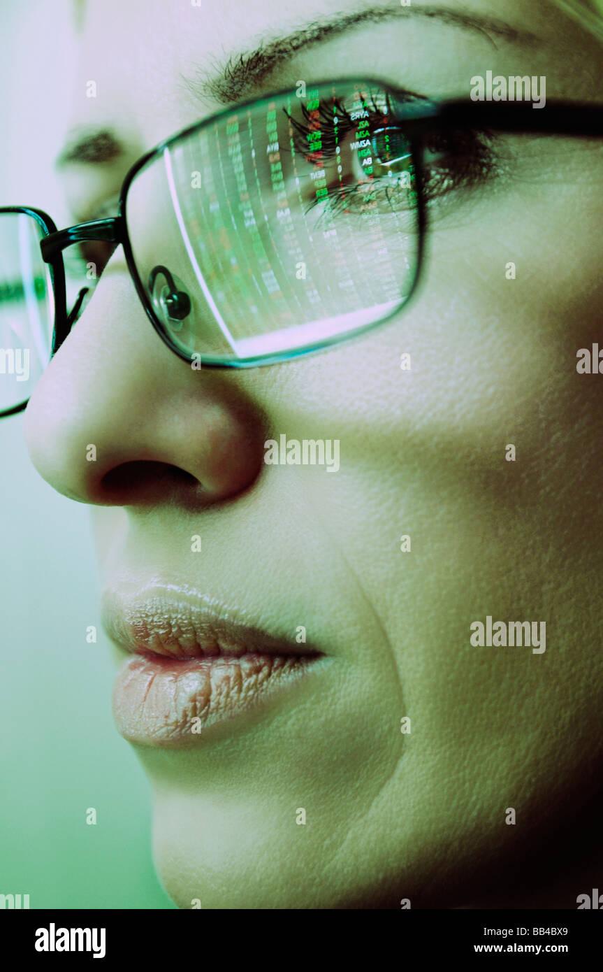 Femmine faccia con occhiali che riflettono un Computer Schermo delle quotazioni di borsa Immagini Stock