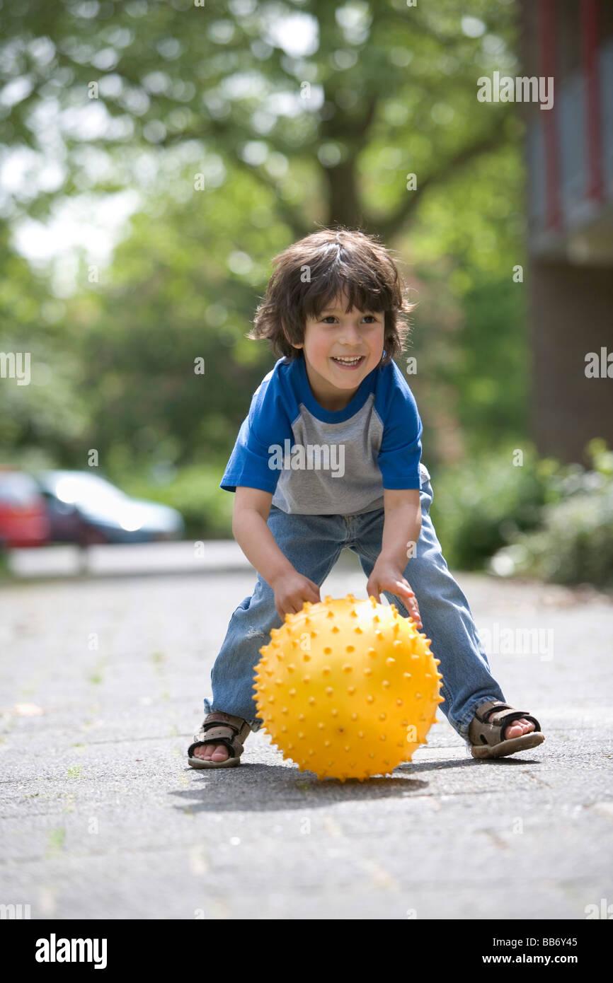 Little Boy giocando con una sfera di colore giallo Immagini Stock