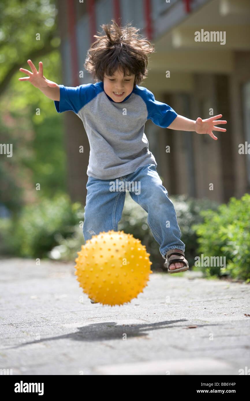 Little Boy calci una sfera gialla Immagini Stock