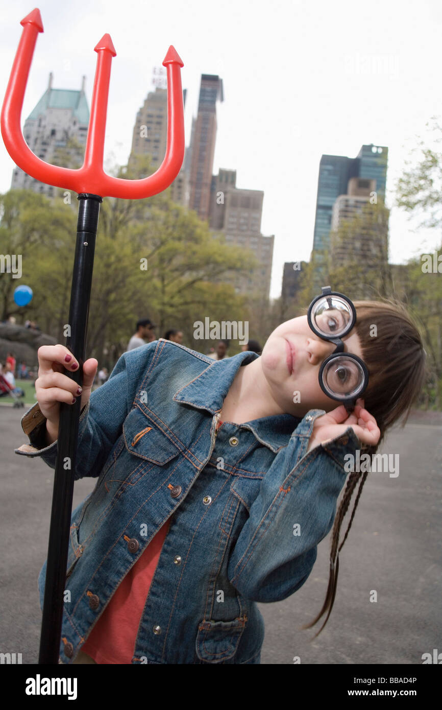 Una giovane ragazza che indossa occhiali buffi e tenendo un devil's forcone Immagini Stock