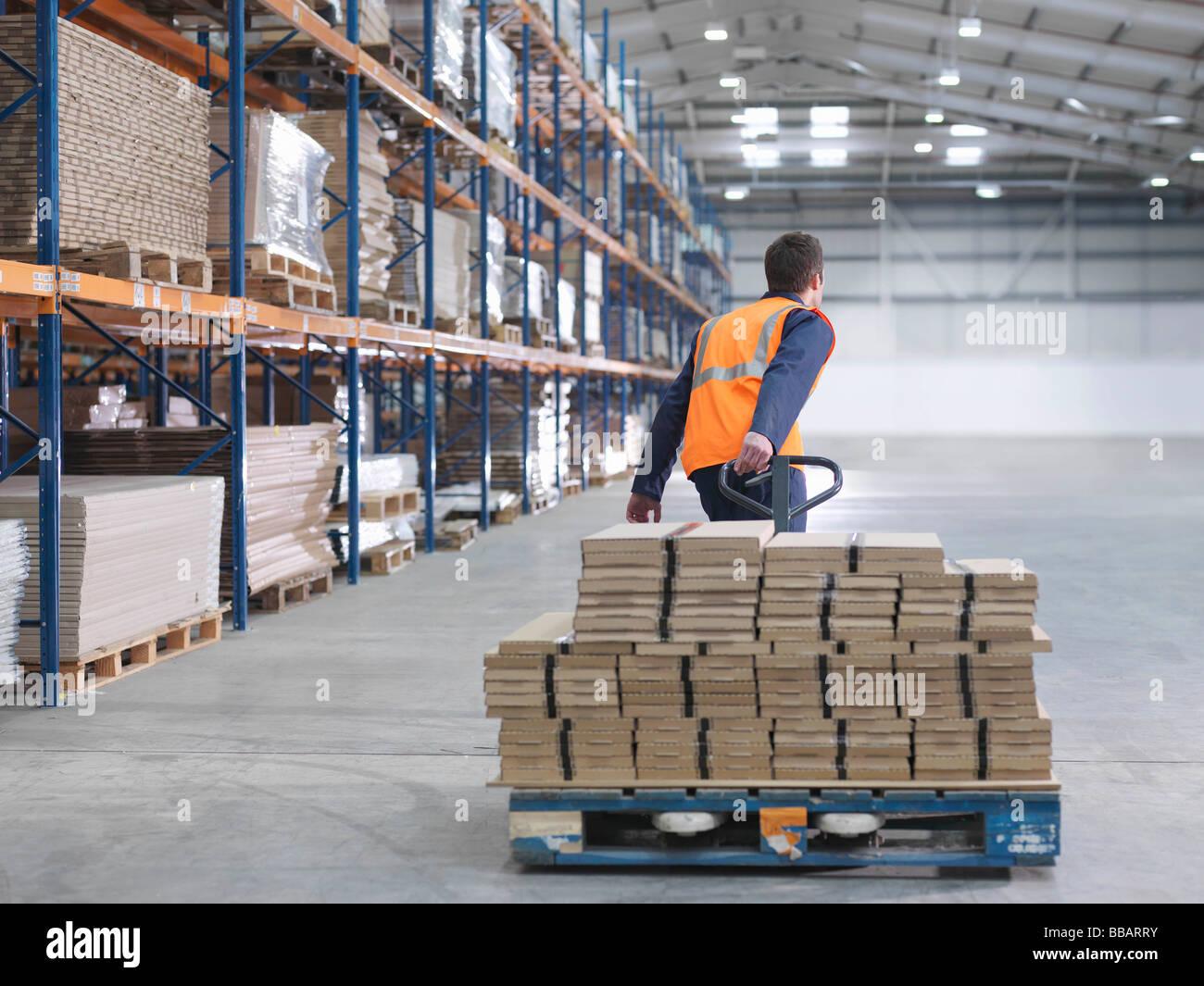 Lavoratore il trasporto di carico in magazzino Foto Stock