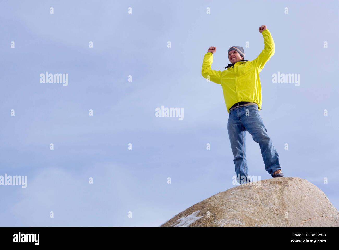 Scalatore celebrando sul picco di montagna Immagini Stock