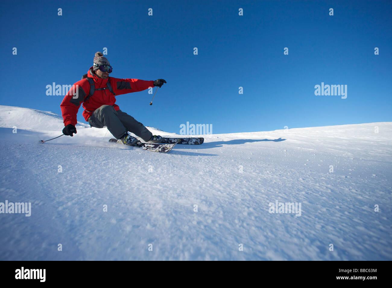 Sciatore girando sulla pista. Immagini Stock