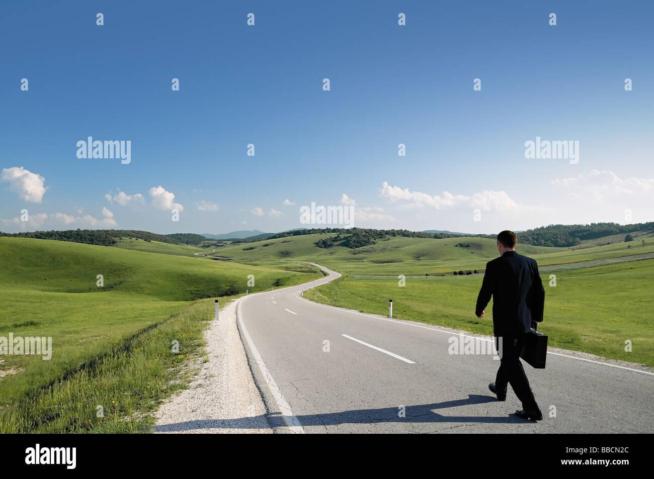 Imprenditore a piedi lungo un paese isolato su strada vista posteriore Immagini Stock