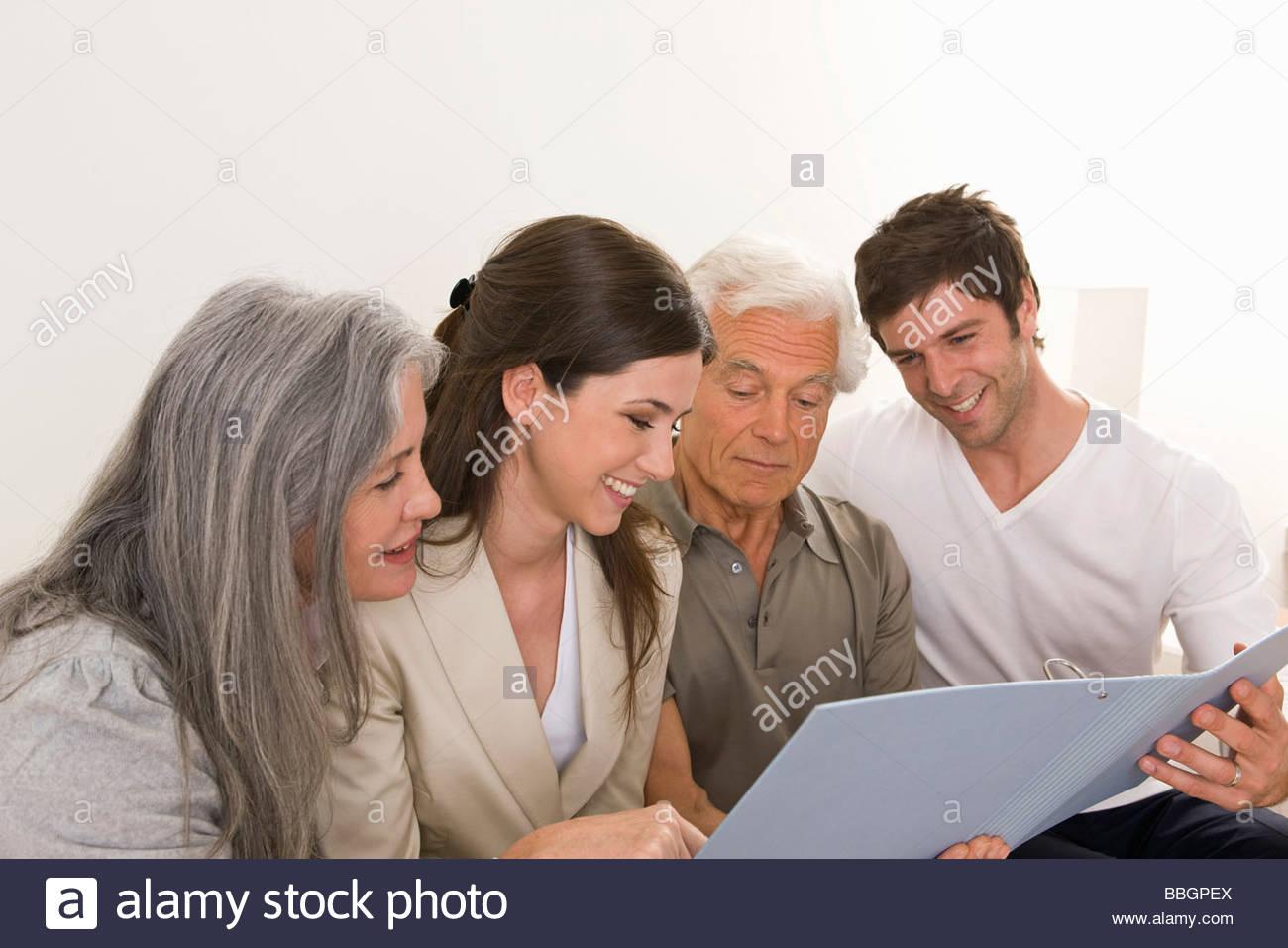 Famiglia con adulto prole a casa cercando nella cartella Immagini Stock