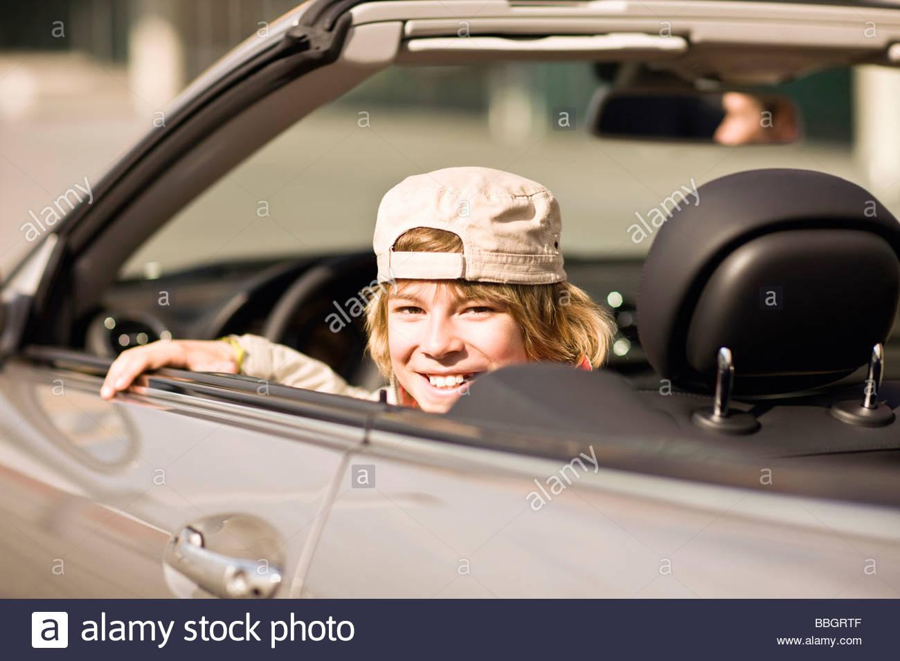 Felice di pre-adolescenti ragazzo seduto cabrio, Monaco di Baviera, Germania Immagini Stock