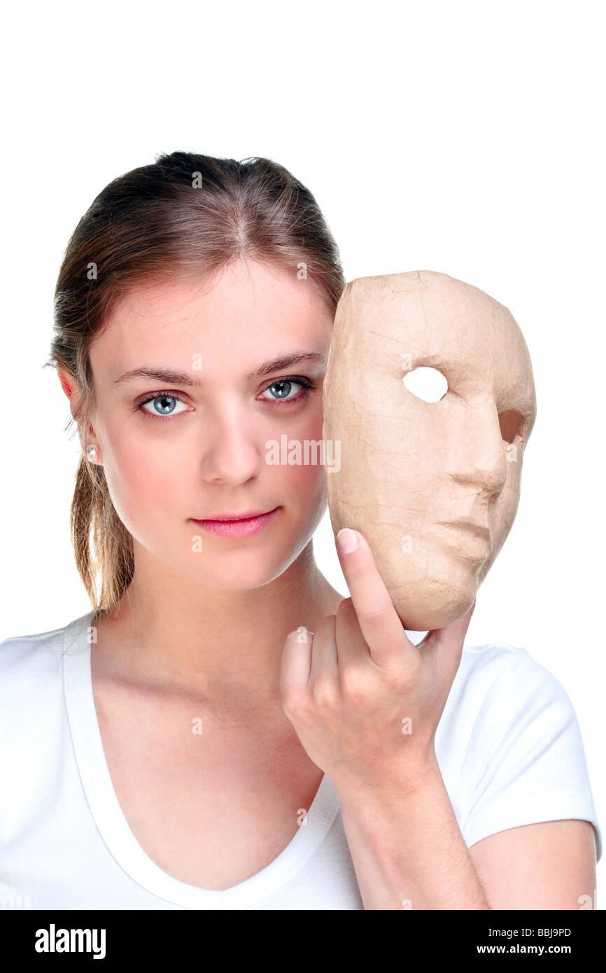 Giovane donna mantenendo una maschera di fronte il suo volto isolato su uno sfondo bianco Immagini Stock
