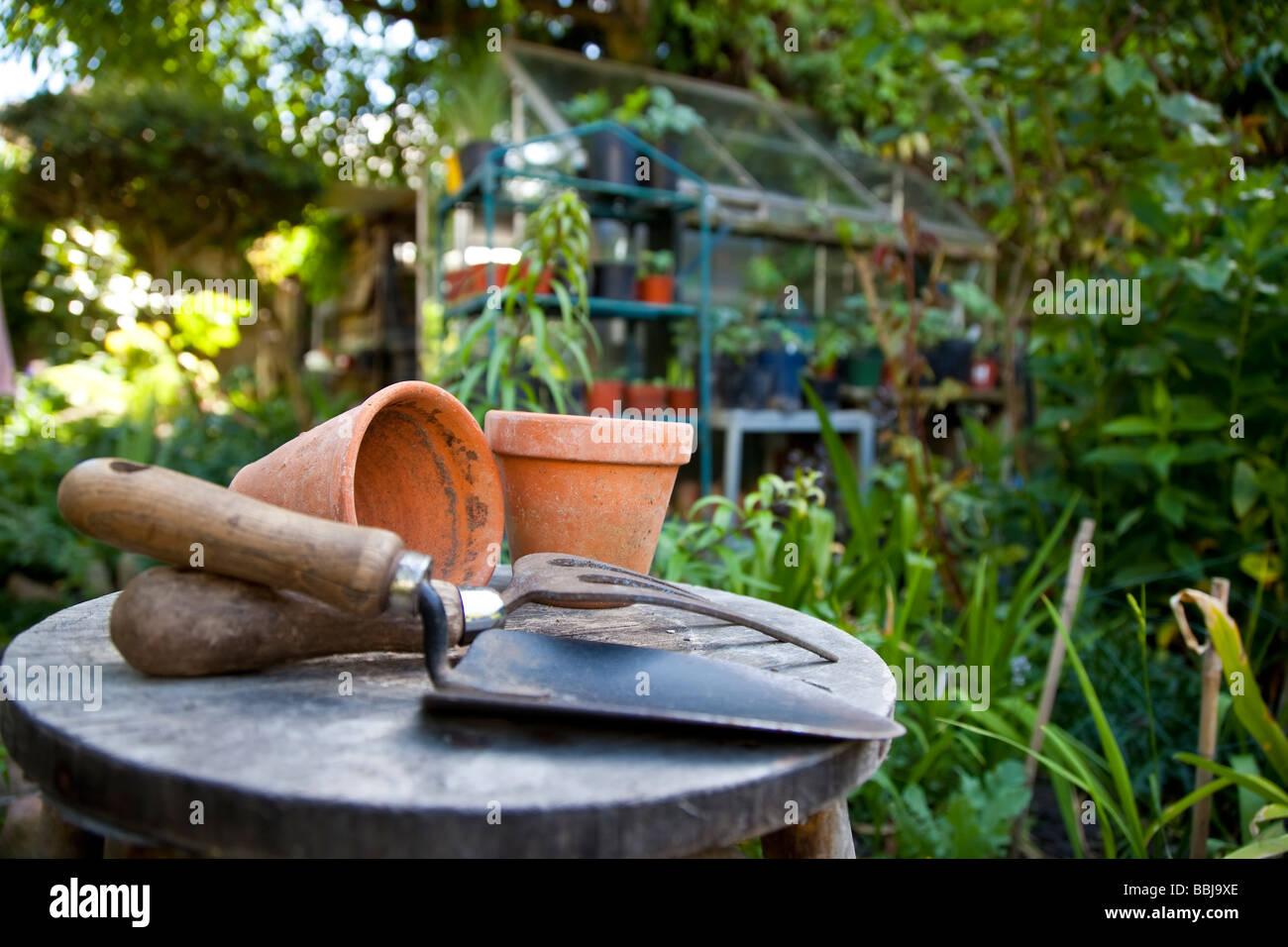 Utensili da giardinaggio e vasi di fiori appoggiati su uno sgabello