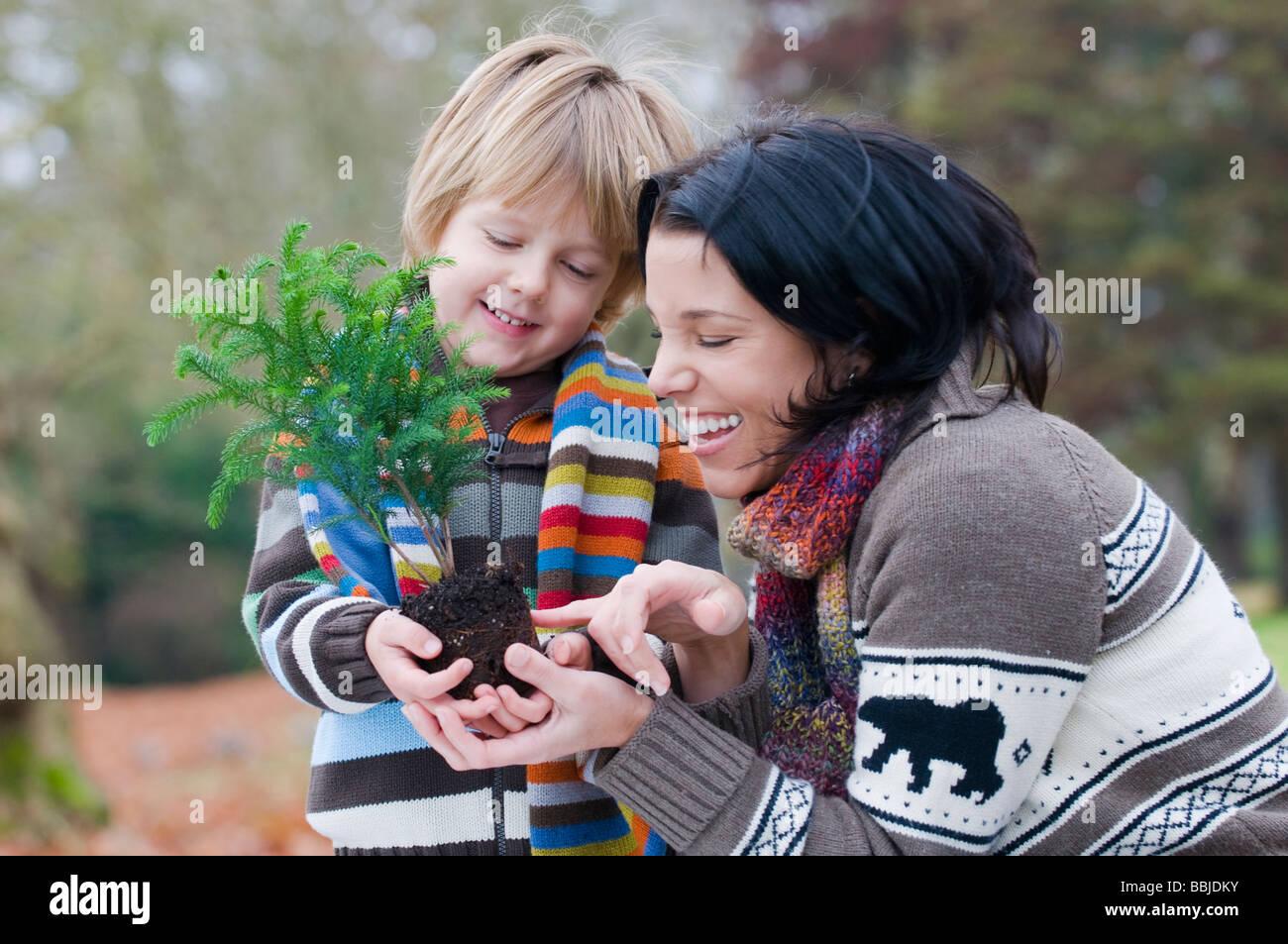 La madre e il ragazzo giovane azienda piccolo albero pronto per impianto, Vancouver, British Columbia Foto Stock