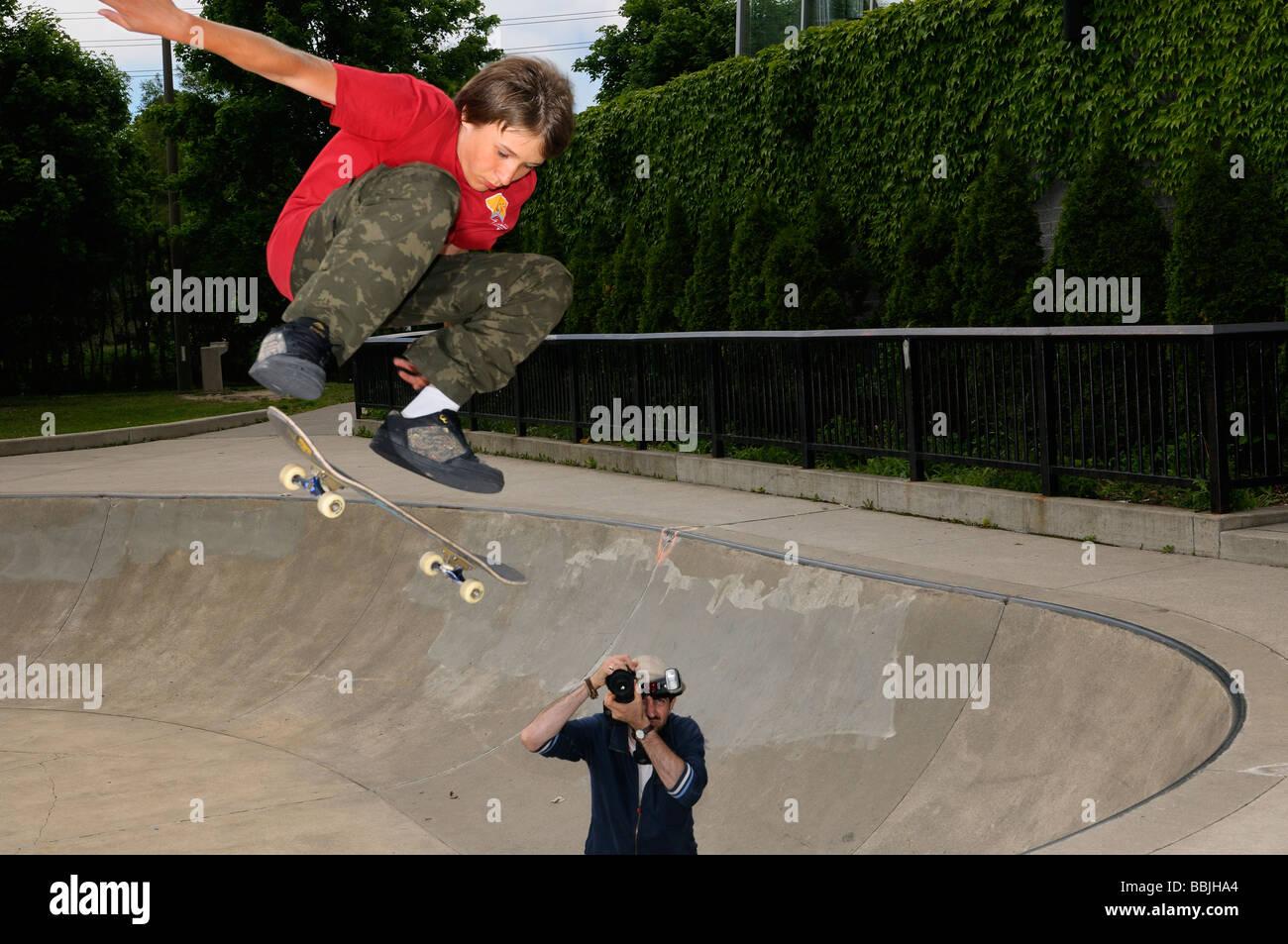 Ragazzo giovane airborne su uno skateboard al di sopra di un recipiente di calcestruzzo in un esterno di Toronto Immagini Stock