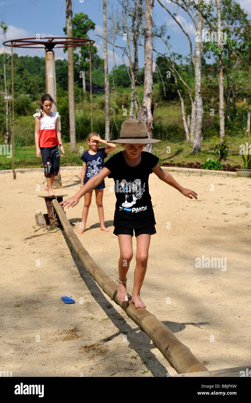 7 anno di età bambino indossando Episteme hat, bilanciamento sulla lunghezza di bambù nel parco giochi. Immagini Stock