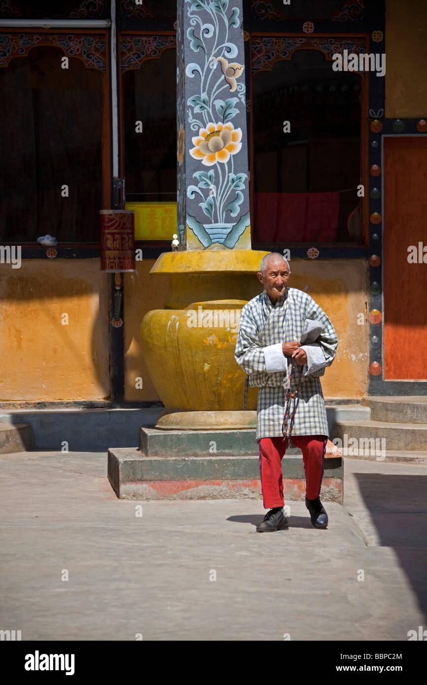 Uomo che prega tenendo la preghiera mulino in Tashi Dzong Chho, Thimphu Bhutan Asia Immagini Stock