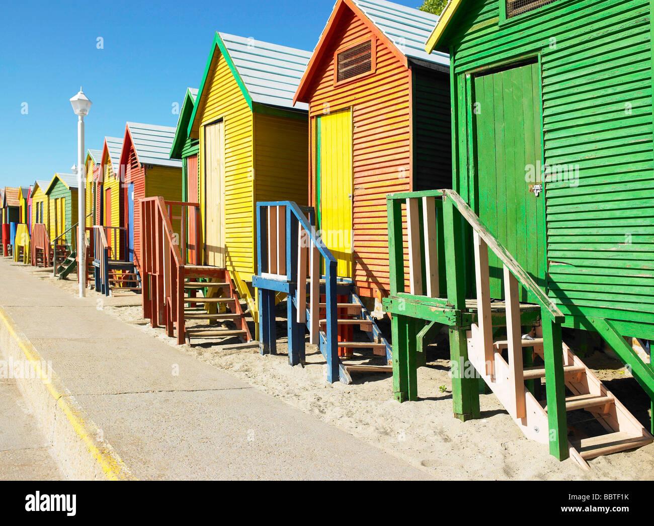 Fila di cabine sulla spiaggia, in colori luminosi Immagini Stock