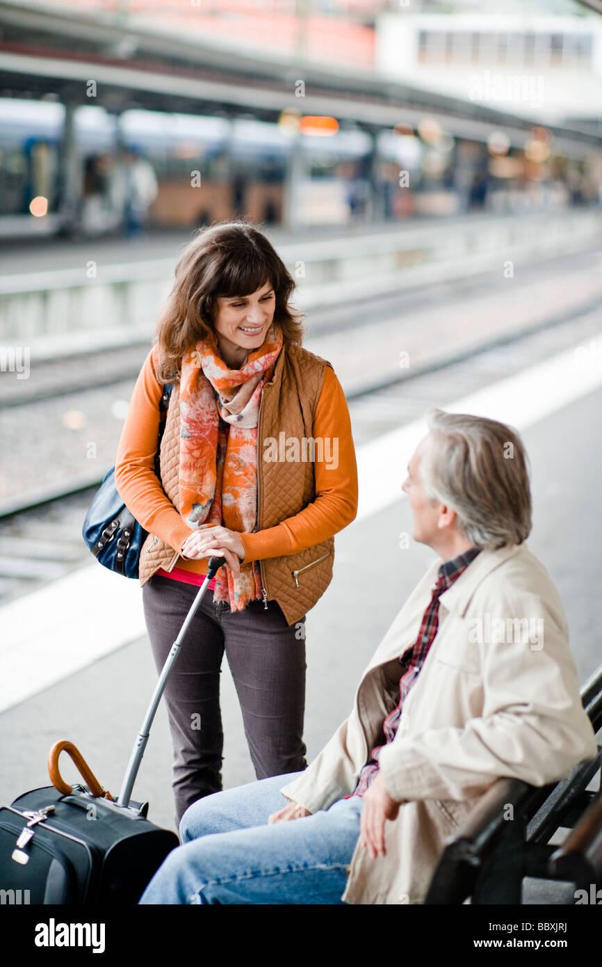 Un uomo e una donna su una piattaforma in corrispondenza di una stazione ferroviaria in Svezia. Immagini Stock