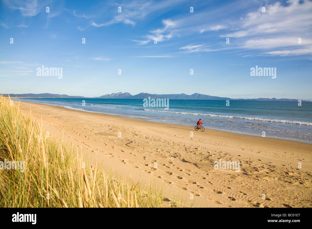 Una donna godendo di un giro in bici su nove miglia di spiaggia sulla costa est della Tasmania, Australia. Immagini Stock